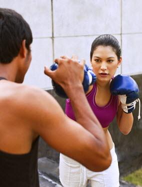 AR3329200025 Nai Yang Beach, Thailand, Phuket: Young woman practicing thai boxing (muay thai) at Indigo Pearl resort, Phuket, Thailand.
