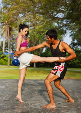AR3329200026 Nai Yang Beach, Thailand, Phuket: Young woman practicing thai boxing (muay thai) at Indigo Pearl resort, Phuket, Thailand.