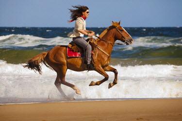 AR3861200021 Punta del Este, Uruguay, Maldonado: A woman rides a horse at the beach in Punta del Este, Uruguay.