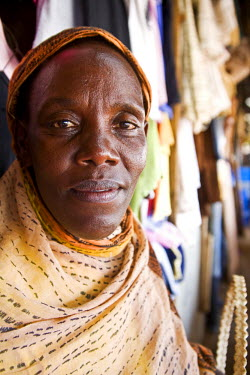 RW1173AW Kigali, Rwanda. An old woman trades traditional clothes in Kimironko market. (MR).