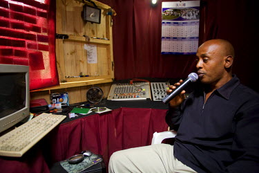 RW1174AW Kigali, Rwanda. Radio DJ produces the in-house radio for Kimironko market, the radio is used to communicate AIDS education. (MR).