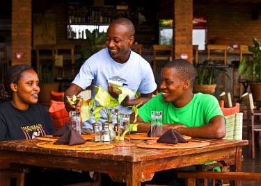 RW1181AW Kigali, Rwanda. Customers enjoy cocktails in a new restaurant. (MR).