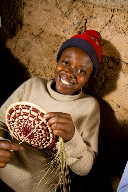 RW1186AW Kigali, Rwanda. A member of a weaving cooperative makes traditional baskets. (MR).