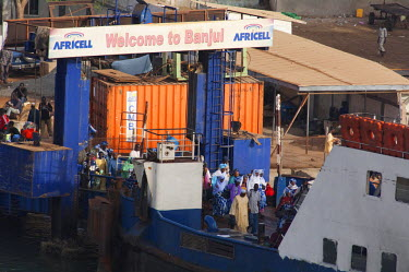 AF18_CMI0029 Africa, Gambia. Capital city of Banjul. Port area of Banjul. Crowds of passengers getting on ferry boat docked in Banjul.