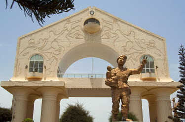 AF18_CMI0055 Africa, Gambia. Capital city of Banjul. Arch 22, 114 foot high archway commemorates bloodless military coup of July 22, 1994. Statue of soldier in uniform with child.