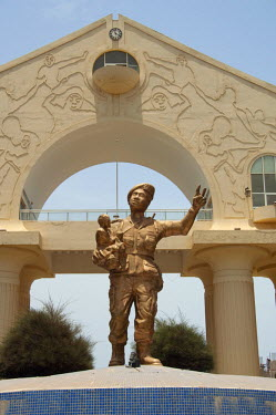 AF18_CMI0057 Africa, Gambia. Capital city of Banjul. Arch 22, 114 foot high archway commemorates bloodless military coup of July 22, 1994. Statue of soldier in uniform with child.