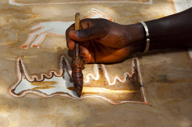AF18_CMI0079 Africa, Gambia. Capital city of Banjul. Local batik workshop, artist demonstration on how to paint cloth with hot wax on copper wire brush to make batik textiles.