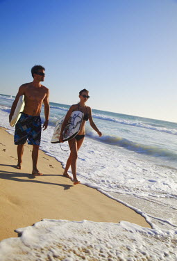 AUS1557AW Young couple walking on Brighton beach with bodyboards, Perth, Western Australia, Australia (MR)