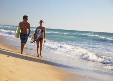 AUS1558AW Young couple walking on Brighton beach with bodyboards, Perth, Western Australia, Australia (MR)