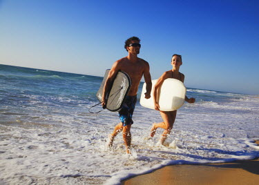 AUS1559AW Young couple running out of ocean with bodyboards, Brighton beach, Perth, Western Australia, Australia (MR)