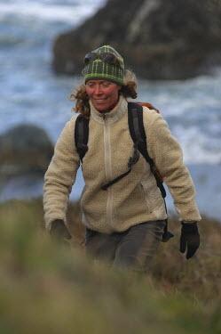 AR3933100033 Port Orford, Oregon, USA. A woman hikes near a beach on the Oregon Coast.