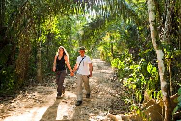 AR3970300008 Sandoval Lake, Amazon Rainforest, Puerto Maldanado, Peru., Peru. Recent, young, newlyweds enjoy themseleves while walking down a path in the amazon rainforest.