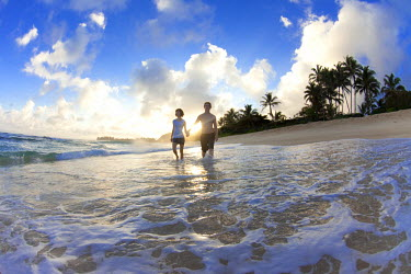 AR3986000005 north shore of Oahu, Hawaii, USA. A couple walking along the beach in the sunrise in Hawaii.