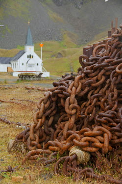 AN02_CMI0260 South Georgia Island. Grytviken. Old anchor chain with Whaler's Church in distance.Typical Norwegian style, southern most church, 1913.