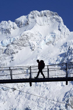 AU02_DWA6462 Hiker on Hooker River Footbridge & Mt Sefton, Aoraki / Mt Cook National Park, Canterbury, South Island, New Zealand