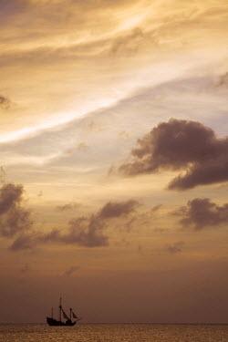 CA42_PSO0029 Cayman Islands, Grand Cayman Island, Setting sun silhouettes yacht sailing through Caribbean Sea
