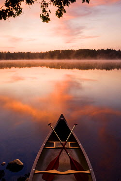 US30_JMO1241 A canoe rests on the shore of Pawtuckaway Lake at dawn as seen from Horse Island in New Hampshire's Pawtuckaway State Park, USA