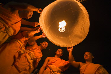 THA0260 Thailand, Chiang Mai, San Sai.  Monks launch a khom loi (sky lantern) during the Yi Peng festival.  The ceremony is a Lanna (northern Thailand) tradition and coincides with Loi Krathong festivities....