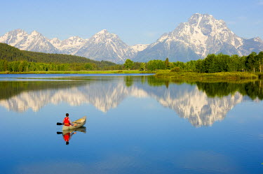 AR9239900015 A man canoeing on a calm river at sunrise with huge snow covered mountains in the background, Wyoming, USA