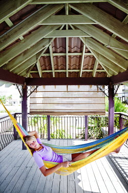 AR4181600026 A girl relaxes on a porch in a hammock  with her arm behind her head