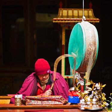 IND6556 India, Ladakh, Hemis. Monk reciting prayers to the slow rhythm of a drum at Hemis Monastery.