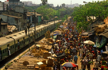 IND6665 India, West Bengal, Kolkata (aka Calcutta). Crowds throng a market adjacent to a railway line.