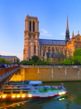 FRA7062AW France, Paris, Notre Dame Cathedral and tour boat on River Seine at dusk