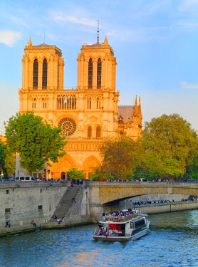 FRA7064AW France, Paris, Notre Dame Cathedral and tourist boat on River Seine at sunset