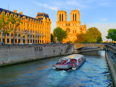 FRA7065AW France, Paris, Notre Dame Cathedral and tourist boat on River Seine at sunset