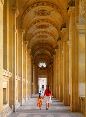 FRA7079AW France, Paris, The Louvre, woman and girl aged 8 walking through arched promenade (MR)