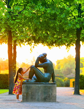 FRA7093AW France, Paris, Jardin des Tuileries, girl aged 8  looking at statue (MR)