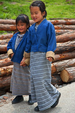 BHU1367 Two schoolgirls go to school in Mongar, a small hilltop town in East Bhutan.   All children attending school must wear national dress which, in the case of girls, is a long striped dress called kira a...