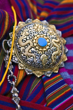 BHU1443 The beautiful shoulder clasp of a Bhutanese woman wearing national dress called kira.