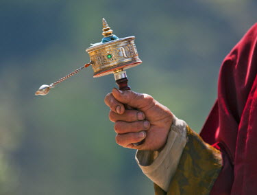 BHU1461 A Buddhist spins his hand-held prayer wheel in a clockwise direction with the help of a weighted chain attached to it.  Each turn is the equivalent of reading the prayers or mantras within.