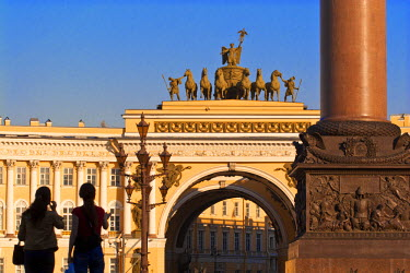 RU02170 Russia, St Petersburg, Palace Square, Tourist looking at Triumphal Arch and classical yellow-and-white building of the former Imperial Army General Staff - to the left is Alexander Column