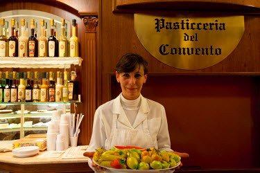 IT9566 Sicily, Italy, Western Europe; The proud owner of Maria Grammatico's Pasticceria del Convento  sweet shop which is one of the most notable in Erice, holding a plate of Marzipan fruits