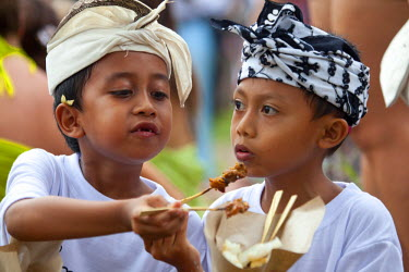 IDA0209 Bali, Ubud. Two young friends share chicken satay at the Nyepi celebrations in Ubud.