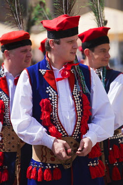 POL1083 Poland, Cracow. Polish boys in traditional dress preparing to dance in Market Square.