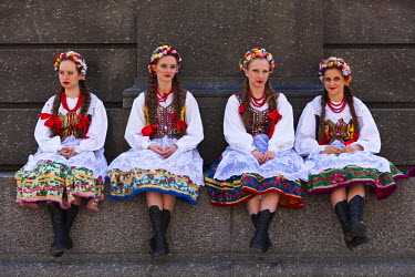 POL1088 Poland, Cracow. Polish girls in traditional dress sitting at the base of the statue of Adam Mickiewicz, preparing to dance in Market Square.