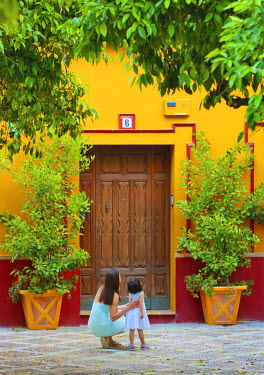 SPA3821AW Spain, Andalucia, Seville, Woman and child infront of traditional doorway (MR)
