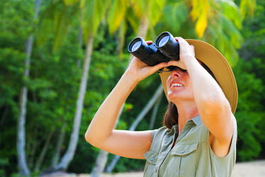 TTB0010AW Trinidad and Tobago, Tobago Island, Englishman's Bay, Woman looking through binoculars (MR)