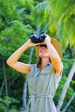 TTB0011AW Trinidad and Tobago, Tobago Island, Englishman's Bay, Woman looking through binoculars (MR)