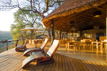 MW1254 Malawi, Majete Wildlife Reserve. The deck and main dining area of  Mkulumadzi luxury safari lodge on the edge of the Shire River.