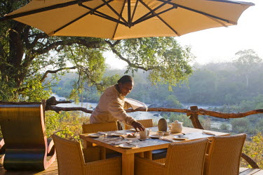 MW1257 Malawi, Majete Wildlife Reserve.  A waitress sets the breakfast table at  Mkulumadzi luxury safari lodge on the edge of the Shire River.