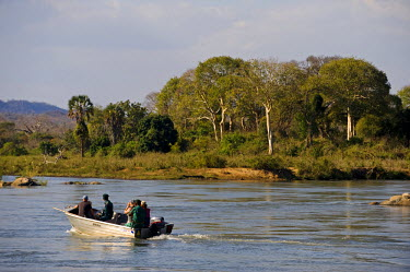 MW1275 Malawi, Majete Wildlife Reserve. A boat of tourists on safari motor past an island in the Shire River looking for wildlife.