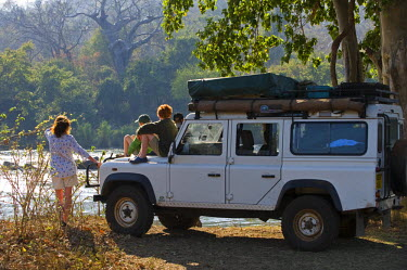 MW1282 Malawi, Majete Wildlife Reserve.  Family on safari look out across the Shirei River from their safari vehicle whilst on a game drive in Majete. (MR)