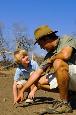 MW1301 Malawi, Majete Wildlife Reserve.  Safari guide points out tracks to a boy on a family safari.