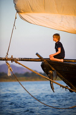 MW1345 Malawi, Lake Malawi National Park.  Young boy enjoys a trip on Lake  Lake Malawi on board the traditional dhow from Pumulani Lodge. (MR)