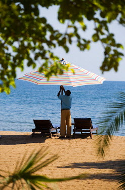 MW1361 Malawi, Lake Malawi National Park.  A waiter at Pumulani Lodge puts up a sun shade.