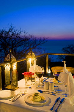 MW1367 Malawi, Lake Malawi National Park.  Dinner laid on the veranda of one of the chalets at Pumulani Lodge with Lake Malawi behind.